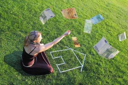 expenditure: Woman sitting on green grass in front of the outline of a house with her hand raised and money floating around her in the air - home ownership savings or expenditure and costs concept