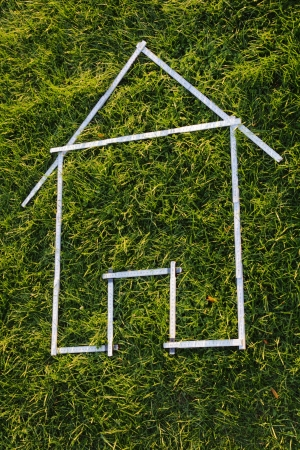 Shape of a house with a white folding rule in green grass Stock Photo