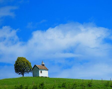 Quaint little chapel with a tiny tower under a solitary tree on the skyiline of a lush green hilltop Stock Photo - 14690814