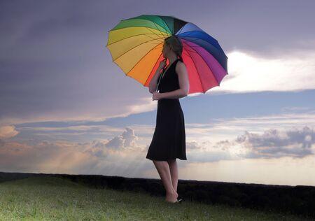 hdr: Femme avec arc-en-couleur parapluie marchant sur une colline verte sous les nuages ??orageux en HDR
