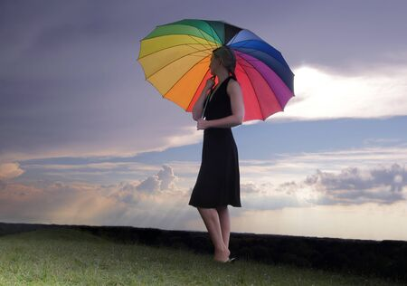 Woman with rainbow coloured umbrella walking across a green hilltop under stormy clouds in HDR