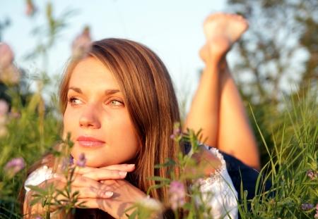 flor silvestre: Mujer atractiva joven tumbado en un prado de flores Foto de archivo