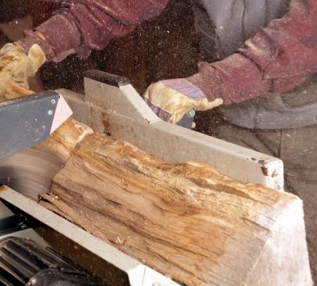 carpenter's sawdust: Man cutting firewood with circular saw Stock Photo