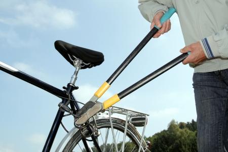 Diefstal snijden van een fietsslot met een tool Stockfoto