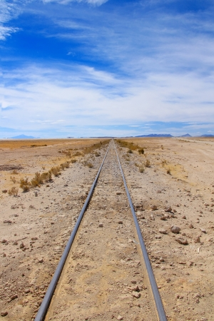 Railway line ending nowhere in blue sky photo
