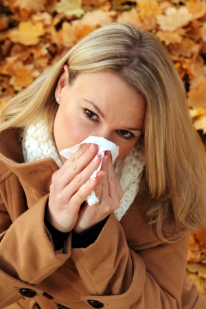 Attractive woman with cold  blowing her nose photo