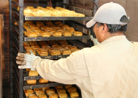 Employee in a bakery removing a rack of  out of an oven Standard-Bild