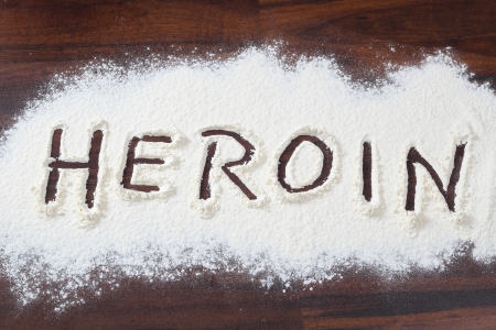 The word heroin written in a white powder
