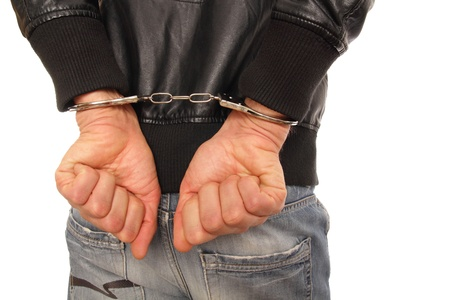 hands behind back: Man in leather jacket and Handcuffs behind his back Stock Photo