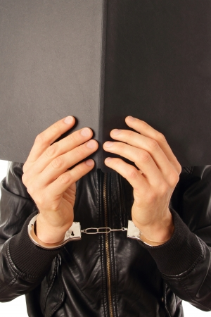 Person in Handcuffs and folder in front of his face Stock Photo - 17206565