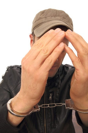 Man with cap and Handcuffs in front of his face photo