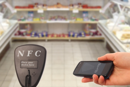 transponder: Woman with NFC smartphone paying in a supermarket