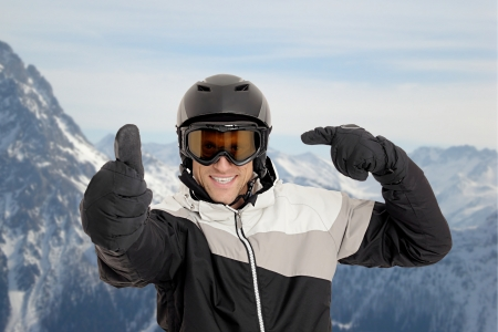 skiing accident: Skier pointing on his helmet in front of mountains