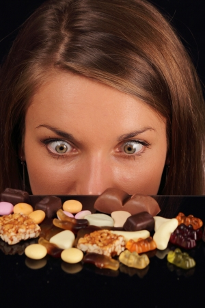 Attractive Woman starring on sweets on a table photo