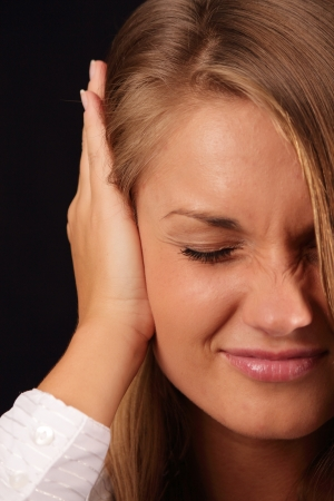 burnout: Young stressed woman with hands on ears