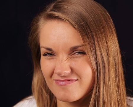 Young atractive woman wrinkeling her noise Stock Photo - 17416936