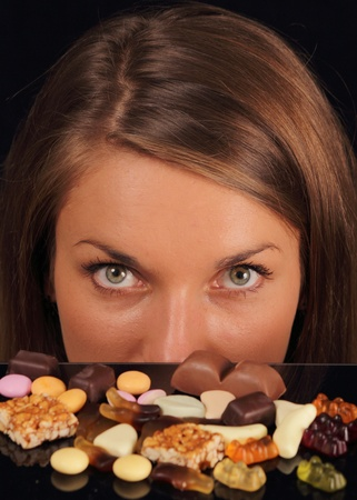 Young attractive woman over sweets looking in camera photo