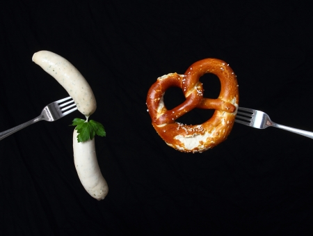 veal sausage: Stylish still life wiht bavarian veal sausage and pretzel on two spoons