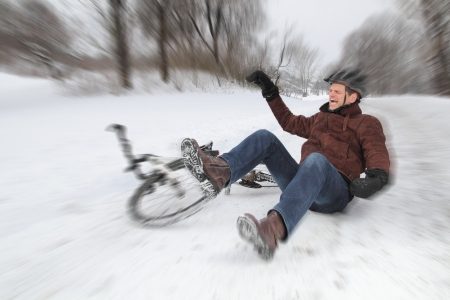 Bicycle accident on a snowy street with a falling man