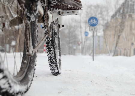 Cyclist in winter with bike road sign low angle photo