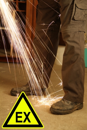 Feets of a worker with sparks of an angle grinder and a sign Stock Photo - 17977220