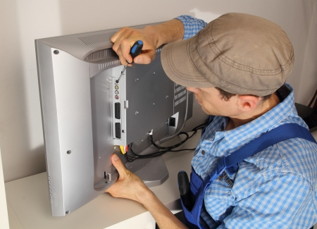 service man: Electrician repairing a TV