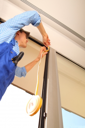 sealing tape: Man sealing window frame Stock Photo