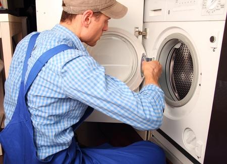 Artisans jeunes réparation machine à laver Banque d'images
