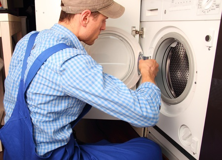 reparaturen: Junge Handwerker Reparatur Waschmaschine Lizenzfreie Bilder