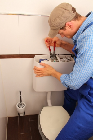 Young craftsman repairing Toilet photo