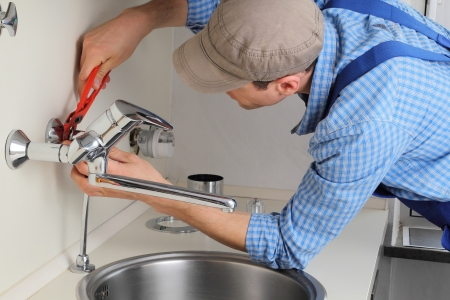 grifo agua: Joven artesano reparando Tap en un Citchen