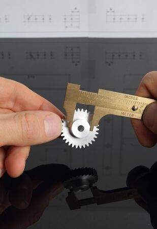 Man measuring cogwheel ony hands photo