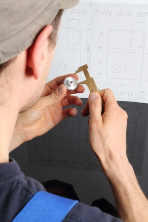 Man measuring cogwhell in front of a drawing Stock Photo - 18766136