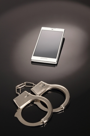 Mobile phone in handcuffs Stock Photo - 18877639
