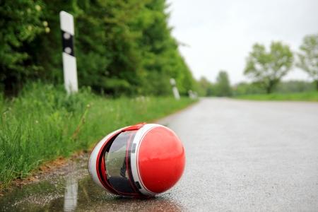 casco de moto: Casco de la motocicleta en una carretera mojada