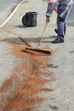 Road maintenance cleaning a trace of oil with a broom