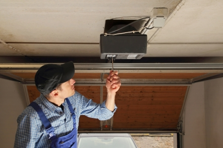 car in garage: Craftsman installing a electrical garage door opener