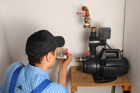 water pump: Man installing a water pump Stock Photo