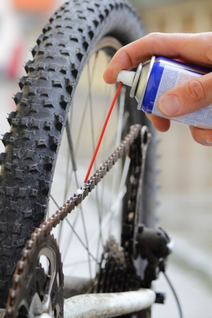 lubricate: Cleaning and oiling a Bicycle chain wiht oil Spray Stock Photo