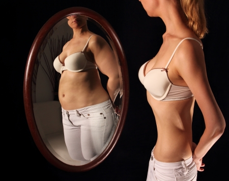thinness: Skinny woman seeing herself fat in a mirrow