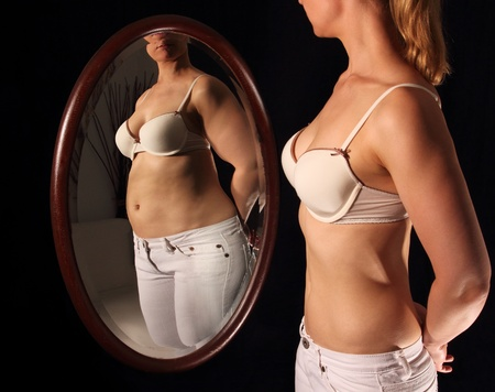 bulimia: Slim woman seeing herself thick in a mirrow