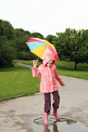 Children with an umbrella in a puddle Stock Photo - 20548465