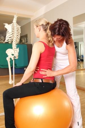 fysiotherapie: Fysiotherapeut met de patiënt werken aan haar lumbale wervelkolom