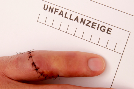 Man with needled finger fills out a accident report photo