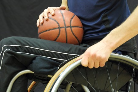 physically:  Wheelchair basketball player with ball on his lap