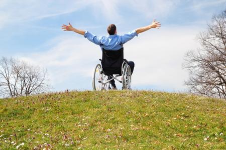 Gelukkig rolstoel gebruiker op een groene heuvel Stockfoto