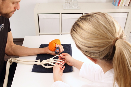 Hand surgeon supports a patient with movement exercises