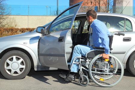 paraplegia: Wheelchair user getting into a car Stock Photo