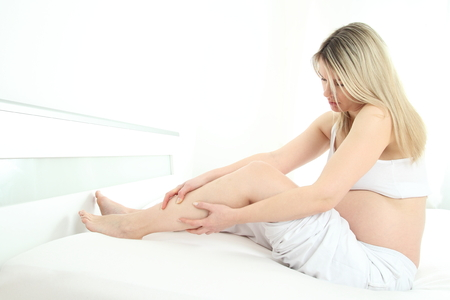 Pregnant woman with calf cramp holding her leg photo