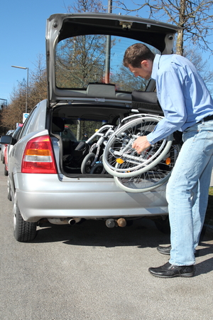 Man packing a wheelchair in a car's trunk Stock Photo - 27550611
